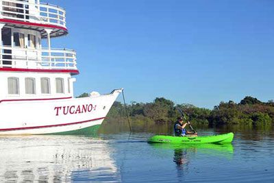 Kayak paddling into the Amazon rainforest from the Motor Yacht Tucano