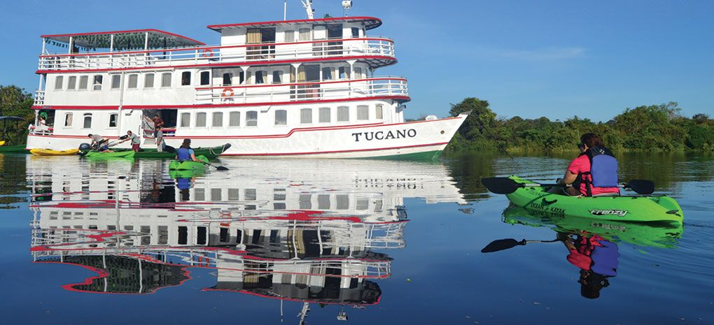 Kayakers paddling on the amazon river toward the Motor Yacht Tucano